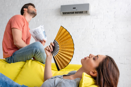 Foto per woman lying with hand fan and man with newspaper sitting on sofa under air conditioner at home - Immagine Royalty Free
