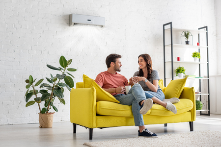 Photo pour happy young couple talking and holding cups while sitting on yellow sofa under air conditioner at home - image libre de droit