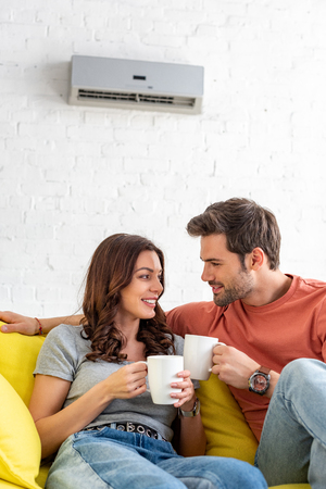 Photo pour happy smiling couple holding cups while sitting under air conditioner at home - image libre de droit