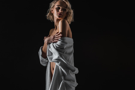 Photo for Beautiful sexy young woman in white bathrobe posing isolated on black background with copy space - Royalty Free Image