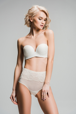 Photo pour Beautiful sexy young woman in lingerie posing isolated on grey background. - image libre de droit