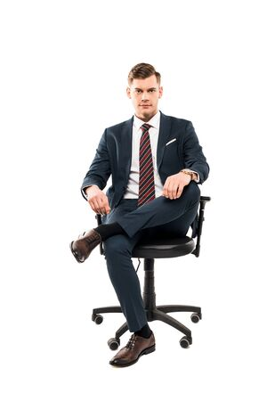 Photo pour Confident businessman sitting on chair and looking at camera isolated on white background - image libre de droit