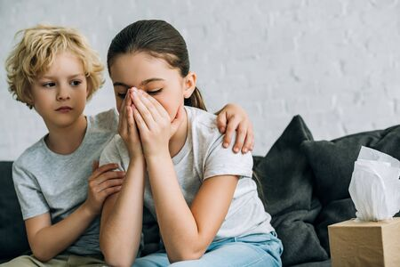 Foto de Little brother consoling crying sister in living room - Imagen libre de derechos