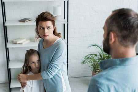 Photo pour Selective focus of scared mother hugging daughter and looking at husband - image libre de droit