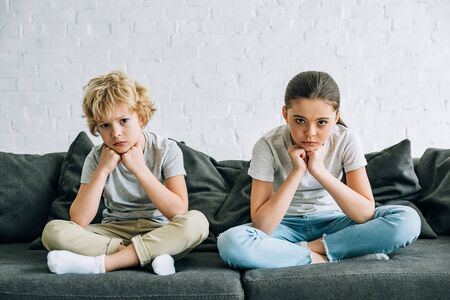 Photo pour Two sad kids sitting on sofa in living room - image libre de droit