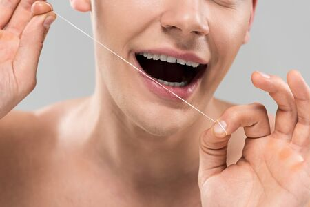Photo pour Cropped view of young man cleaning teeth with dental floss isolated on grey background - image libre de droit