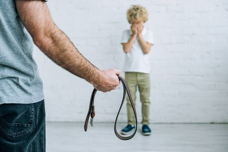 Photo pour Cropped view of father with belt and crying son at home - image libre de droit