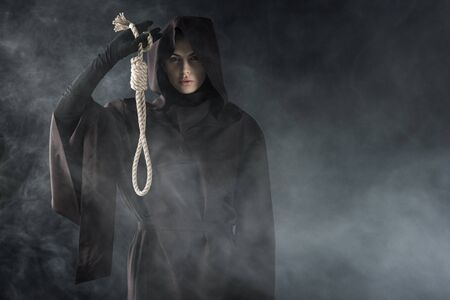 Photo for Front view of woman in death costume holding hanging noose in smoke on black background - Royalty Free Image