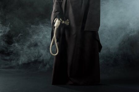 Photo for Partial view of woman in death costume holding hanging noose in smoke on black background - Royalty Free Image