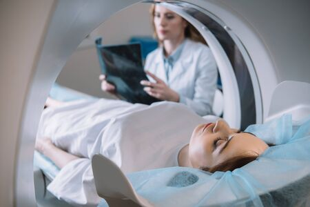 Photo pour Selective focus of radiologist holding x-ray diagnosis while patient lying on ct scanner bed during diagnostics - image libre de droit