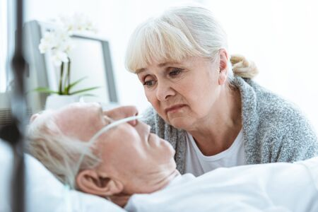 sad senior woman looking at husband in coma in clinic