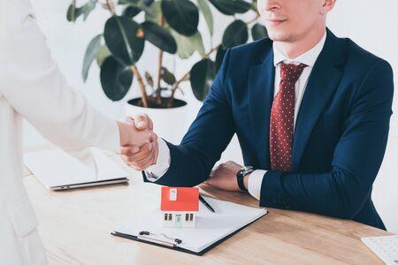 Photo pour cropped shot of businessman in suit shaking hands with client near house model - image libre de droit
