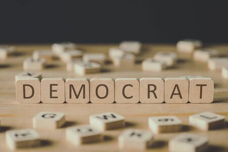 selective focus of word democrat made of cubes surrounded by blocks with letters on wooden surface isolated on black
