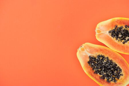 Foto de top view of ripe exotic papaya halves with black seeds isolated on orange with copy space - Imagen libre de derechos