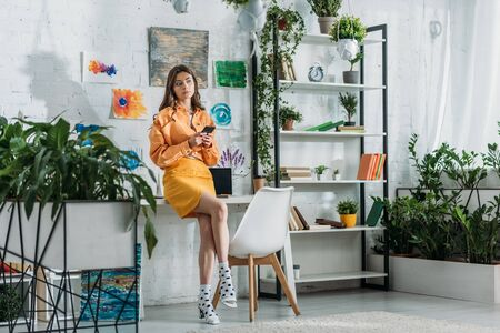 Photo pour stylish grl using smartphone in spacious room decorated with green plants and colorful paintings on wall - image libre de droit