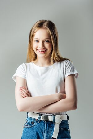 Photo for happy teenage girl with crossed arms looking at camera isolated on grey - Royalty Free Image