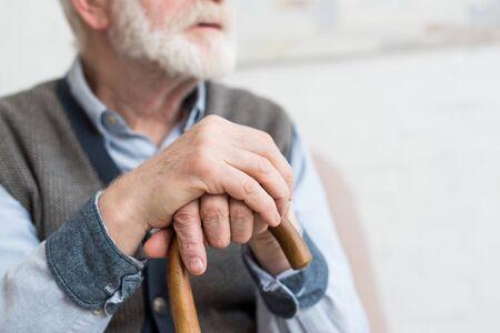 Foto de Cropped view of elderly man with walking stick in hands - Imagen libre de derechos