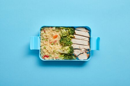 Photo for Top view of lunch box with tasty chicken, risotto and broccoli on blue background - Royalty Free Image