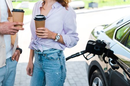 Foto de Cropped view of man standing with hand in pocket near woman holding paper cup at gas station - Imagen libre de derechos