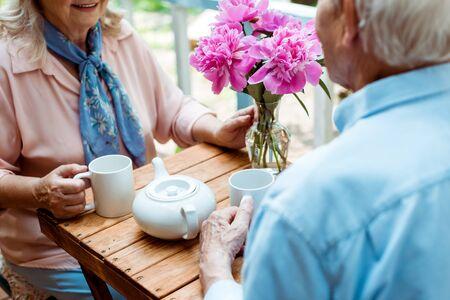 Photo pour Cropped view of senior couple holding cups while sitting near teapot - image libre de droit