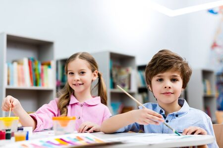 Photo pour Selective focus of cheerful kids looking at camera and holding paintbrushes - image libre de droit