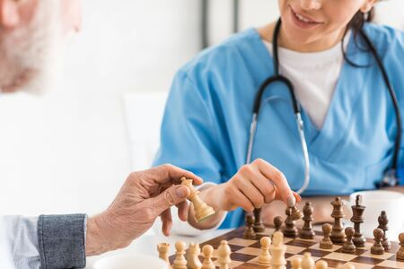 Photo pour Cropped view of nurse and senior man sitting on kitchen, and playing in chess - image libre de droit