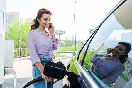 Photo for Happy woman holding fuel pump while refueling car with benzine and talking on smartphone - Royalty Free Image