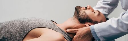 Photo pour Panoramic shot of chiropractor massaging neck of man on grey background - image libre de droit