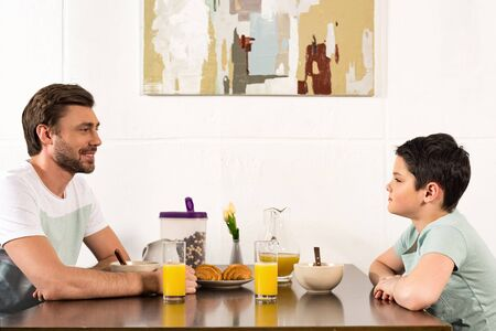 Photo pour Smiling dad and son looking at each other during breakfast - image libre de droit