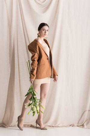 Foto de Beautiful woman with flowers in hands standing on curtain background - Imagen libre de derechos
