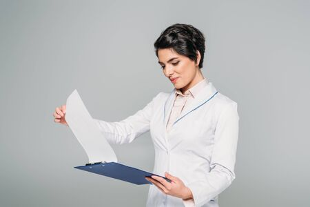 Photo pour Attentive mixed race doctor looking at clipboard with papers isolated on grey background - image libre de droit