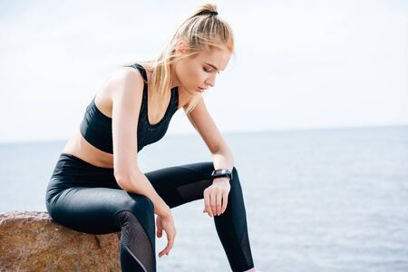 Photo pour Tired blonde sportswoman sitting on stone near sea and looking at fitness tracker - image libre de droit