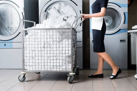 Photo for cropped view of housemaid standing near cart with bedding in laundry - Royalty Free Image