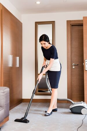 Photo pour brunette housemaid cleaning carpet with vacuum cleaner in hotel room - image libre de droit