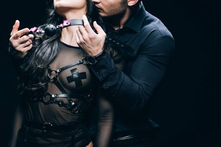 Photo pour Cropped view of handsome young man holding gag near sexy woman in bdsm costume isolated on black background - image libre de droit
