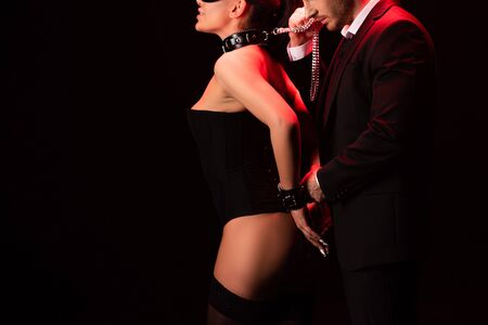 Photo for Cropped view of sexy bdsm couple with handcuffs isolated on black background - Royalty Free Image