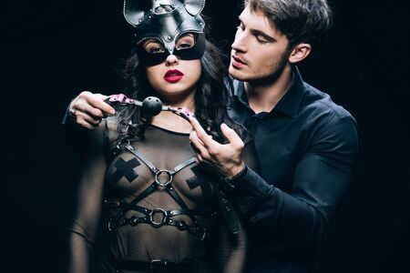 Photo pour Young man holding gag near sexy woman in mask and bdsm costume isolated on black background - image libre de droit