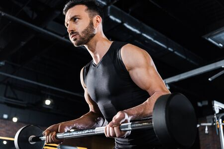 Photo for Low angle view of strong man exercising with heavy barbell in gym - Royalty Free Image
