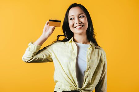 Foto de Cheerful Asian girl holding credit card, isolated on yellow background - Imagen libre de derechos