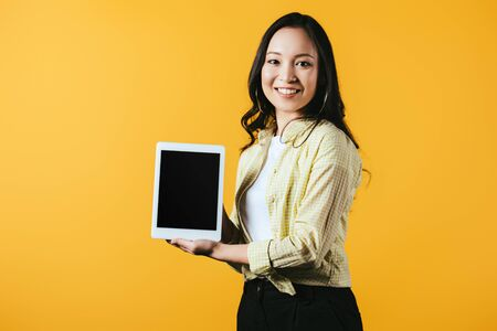 Photo for Smiling Asian woman showing digital tablet with blank screen, isolated on yellow background - Royalty Free Image