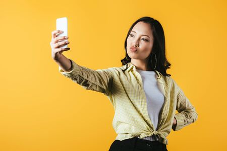Photo pour Attractive Asian girl taking selfie on smartphone isolated on yellow background - image libre de droit