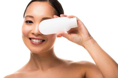 Photo pour Cheerful Asian woman with bottle of lotion, isolated on white background - image libre de droit