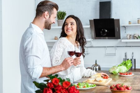 Photo pour Happy man clinking glasses of red wine with smiling woman at kitchen - image libre de droit
