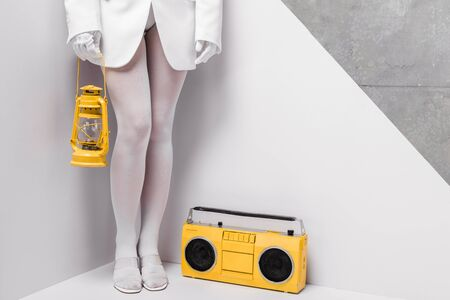 Foto de cropped view of woman posing near retro boombox and holding yellow vintage lamp on white and grey - Imagen libre de derechos