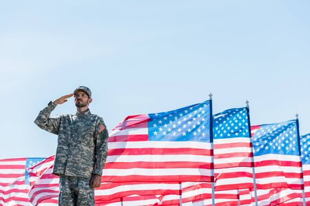 Foto per patriotic soldier in military uniform giving salute near american flags with stars and stripes - Immagine Royalty Free