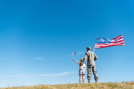 Photo pour back view of child in straw hat and military father holding american flags while standing on grass - image libre de droit