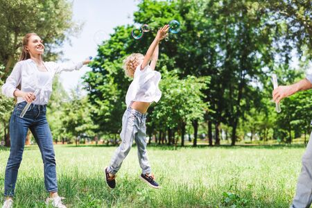 Photo pour mother, father and son playing with soap bubbles in park - image libre de droit