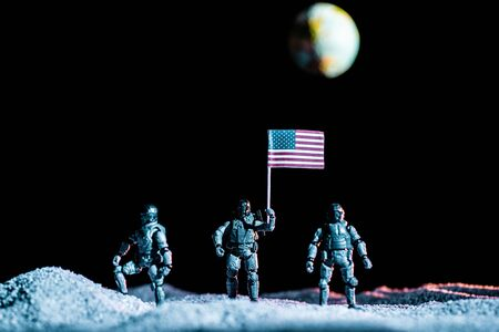 Photo for toy soldiers standing with usa flag on planet in space on black background with planet Earth - Royalty Free Image