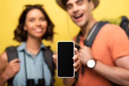 Photo pour selective focus of cheerful woman showing smartphone with blank screen while standing near smiling man on yellow background - image libre de droit