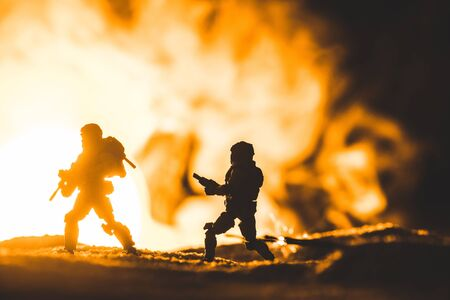 Photo for toy soldiers silhouettes with guns on planet with sun in smoke on background - Royalty Free Image